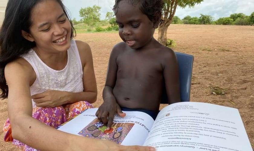 """Rachel lendo o livro de sua autoria """"Adotados em Amor"""" para uma criança Yolngu. (Foto: Reprodução/Eternity)"""