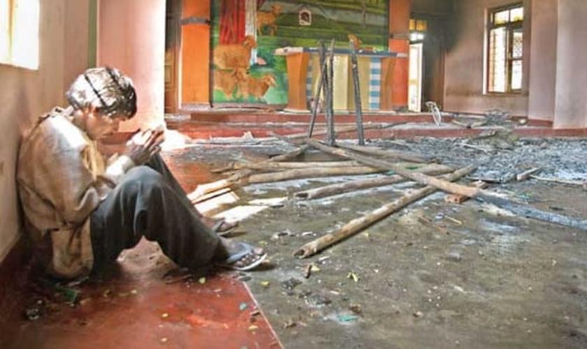 Imagem ilustrativa. Homem indiano orando em igreja destruída. (Foto: Barnabas Fund)