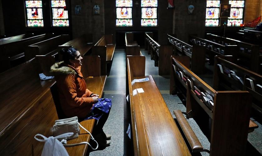 Mulher sentada no banco de uma Igreja Católica vazia em Des Moines, em Iowa, nos EUA. (Foto: Charlie Neibergall/Associated Press)