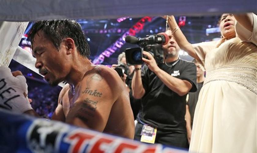 Manny Pacquiao em oração após disputa pelo título dos meio-médios em Macau, na China, em 2014. (Foto: AP)