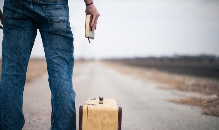 Imagem ilustrativa. Jovem segurando a Bíblia ao lado de uma mala. (Foto: Lightstock)
