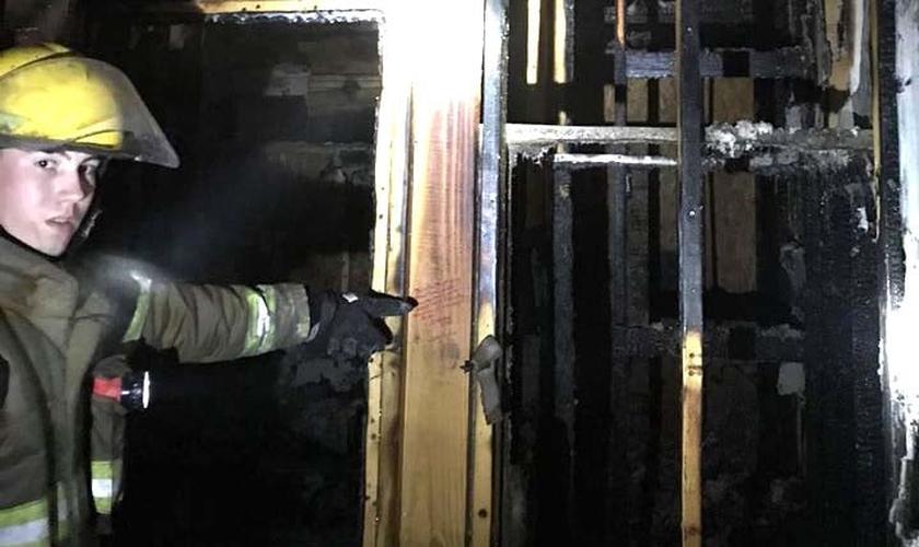 Bombeiro aponta para um dos versículos que não foi atingido pelas chamas. (Foto: Livingston Parish Fire Protection District #2)