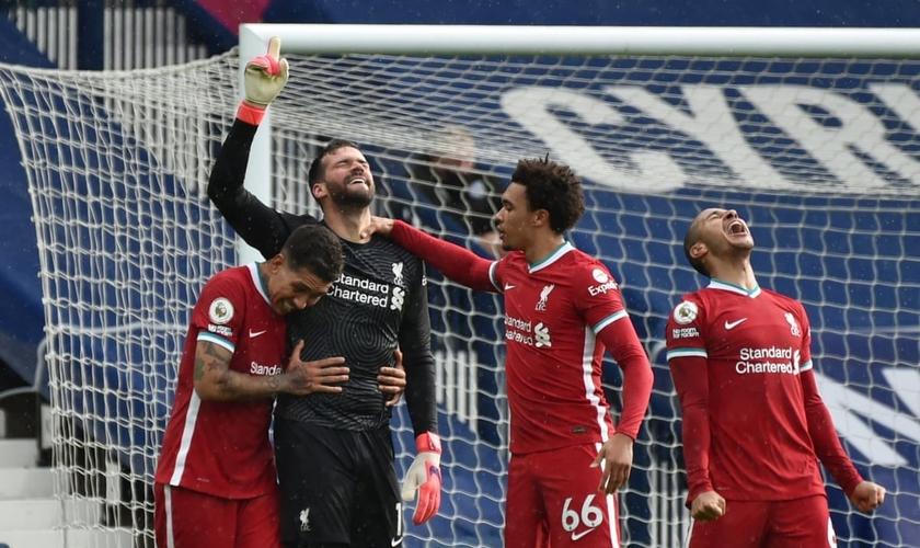 Alisson Becker, goleiro do Liverpool, aponta para o céu após surpreendente vitória. (Foto: Rui Vieira/Reuters)