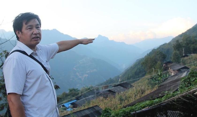 O pregador Pu Zhidui apontando para igreja, duas montanhas adiante, que ele está pastoreando. (Foto: Bible Society).
