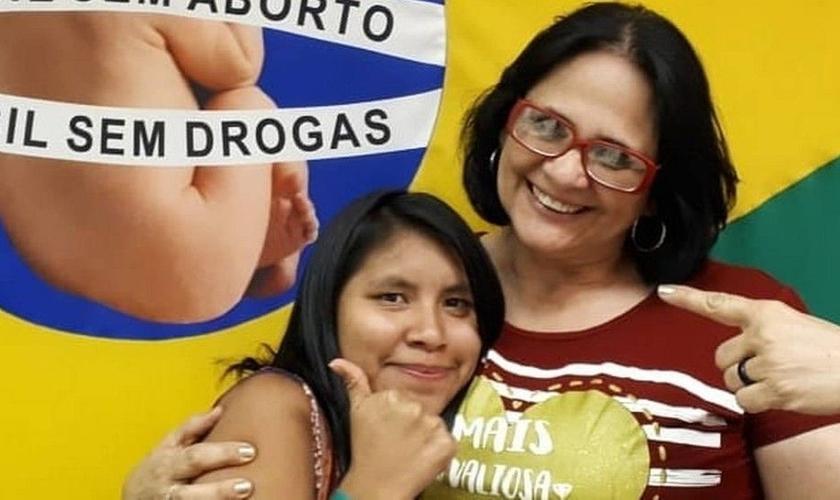 Damares Alves (direita) e Lulu (esquerda) abraçadas em frente à bandeira de uma campanha contra o aborto. (Foto: Instagram)