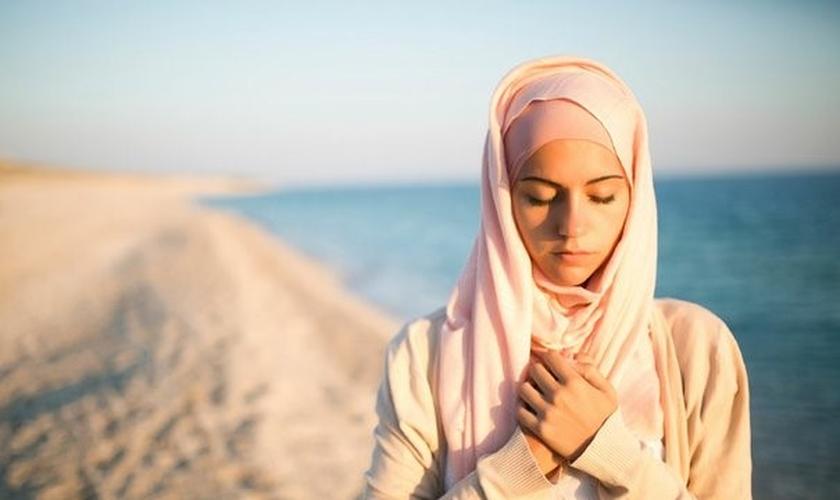Muçulmana em atitude de reflexão na praia. (Foto: Just Between Us Magazine)
