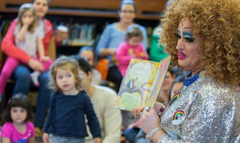 Drag queen conta história para crianças em imagem exibida por propaganda do projeto na TV. (Foto: AP Photo)