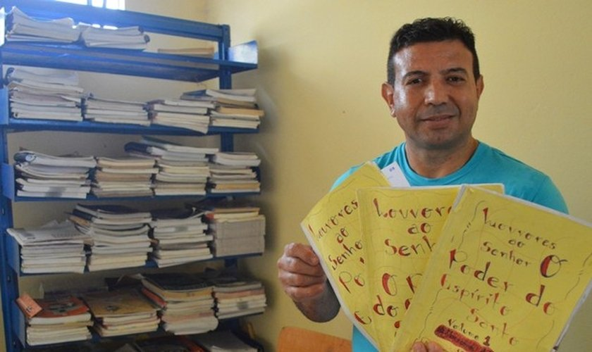 Detento com mostra as histórias que escreveu em sua coletânea. (Foto: Divulgação/Sejus)