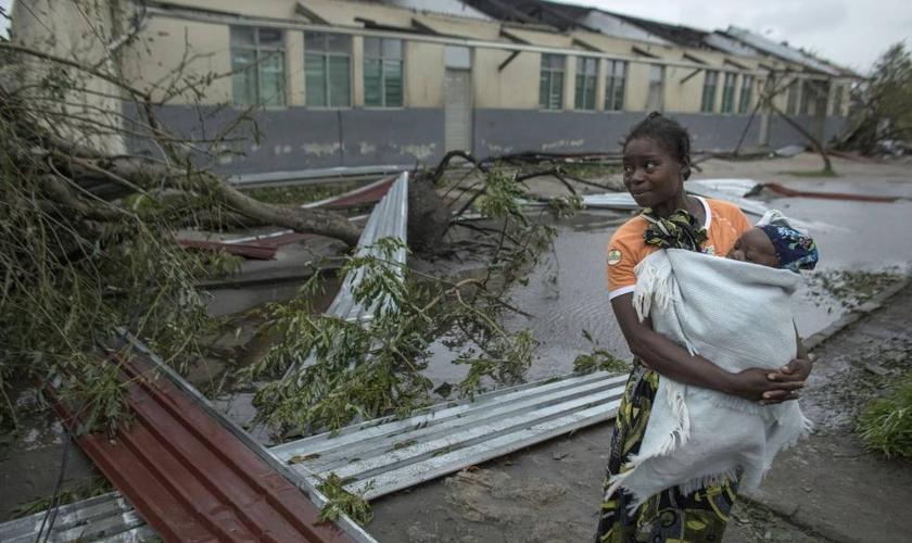 Mulher segura seu filho na cidade da Beira, devastada pelo ciclone Idai em Moçambique. (Foto: J. Estey/AP)