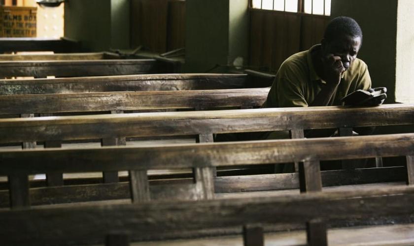 Cristão lê Bíblia sozinho no banco de uma igreja em, Kano, Nigéria. (Foto: Getty Images/Chris Hondros)