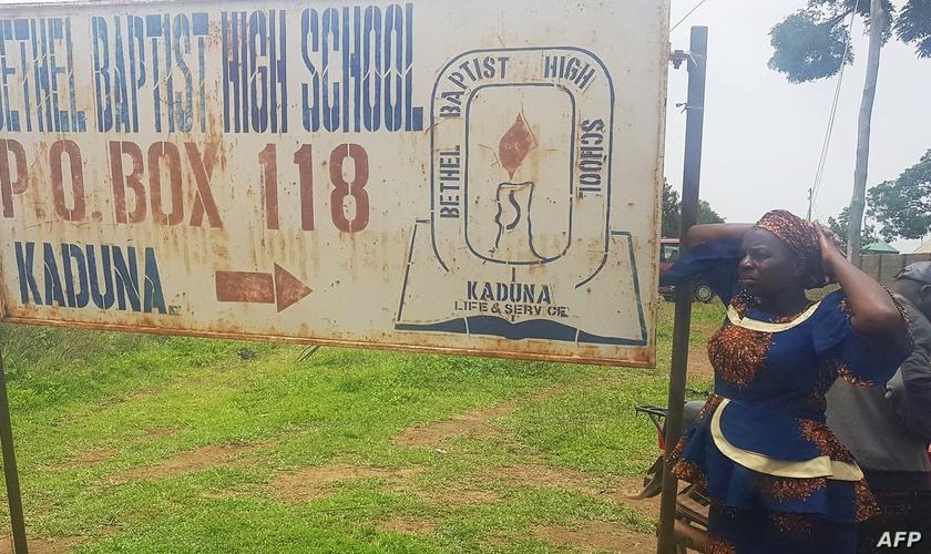 Mãe em frente a uma placa do colégio Betel Batista, em Kaduna. (Foto: Kehinde Gbenga/AFP/Getty Images)
