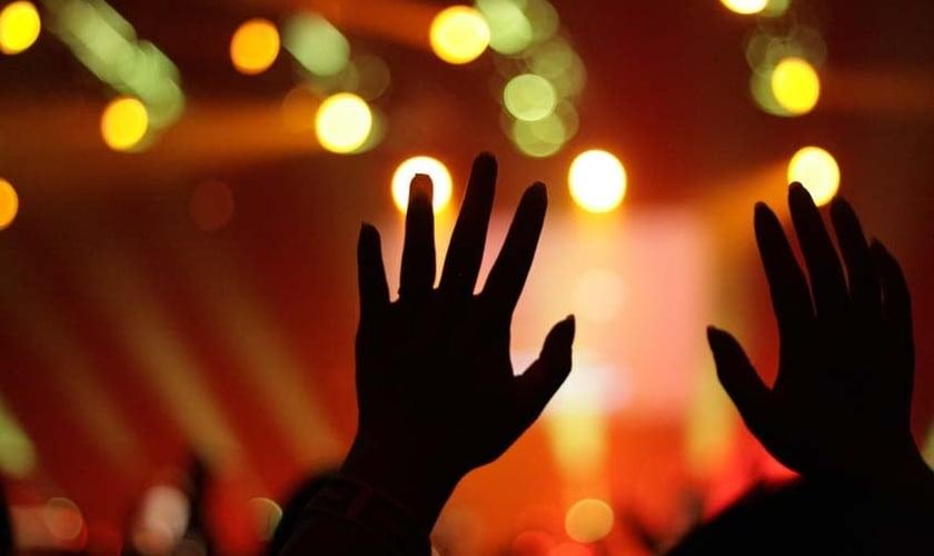 Imagem ilustrativa: mãos levantadas em adoração durante culto.