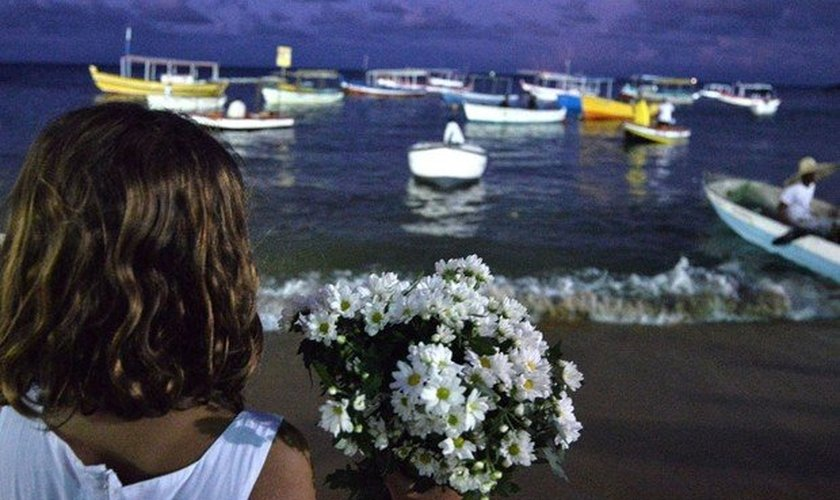 Menina entrega flores como oferenda para Iemanjá, ícone do candomblé. (Foto: Max Haack/Ag. Haack)