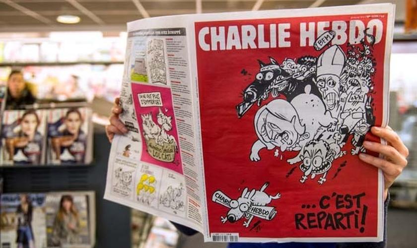 Homem lê a primeira edição do jornal 'Charlie Hebdo' lançada após os ataques de janeiro, nesta quarta-feira (25).