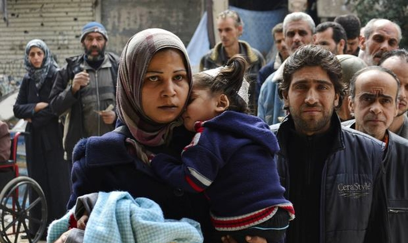 Palestinianos e sírios deixam o campo de refugiados em Yarmouk