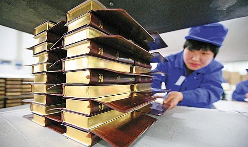 Funcionário da Amity Printing Co. carrega pilhas de Bíblias nas instalações da empresa, em Nanjing, na província de Jiangsu.