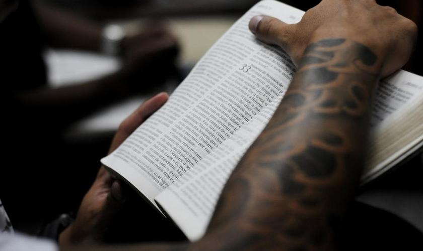 Jovem segurando a Bíblia durante culto em uma igreja evangélica.
