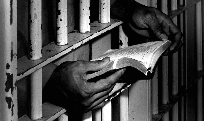 Homem lê bíblia na prisão