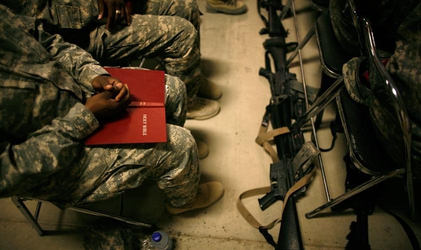 Soldado com a Bíblia Sagrada no colo durante reunião. (Foto: Associated Press)