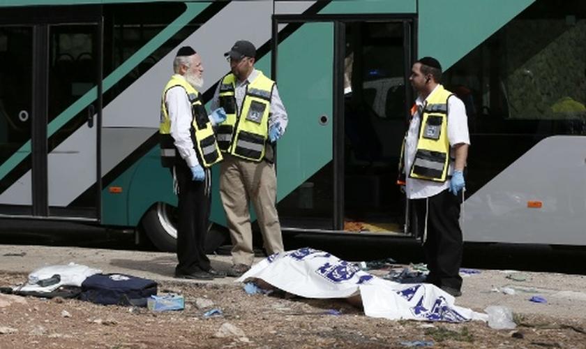 Forças de segurança israelenses conversam ao lado de corpo após ataque a tiros contra um ônibus próximo ao bairro palestino de Jabal Mukaber, em Jerusalém Oriental. (Foto: Thomas Coex/AFP)