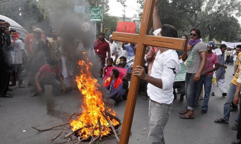 Membro da comunidade cristã paquistanesa segura uma cruz durante um protesto para condenar ataques contra igrejas. (Foto: Reuters/Mohsin Raza)