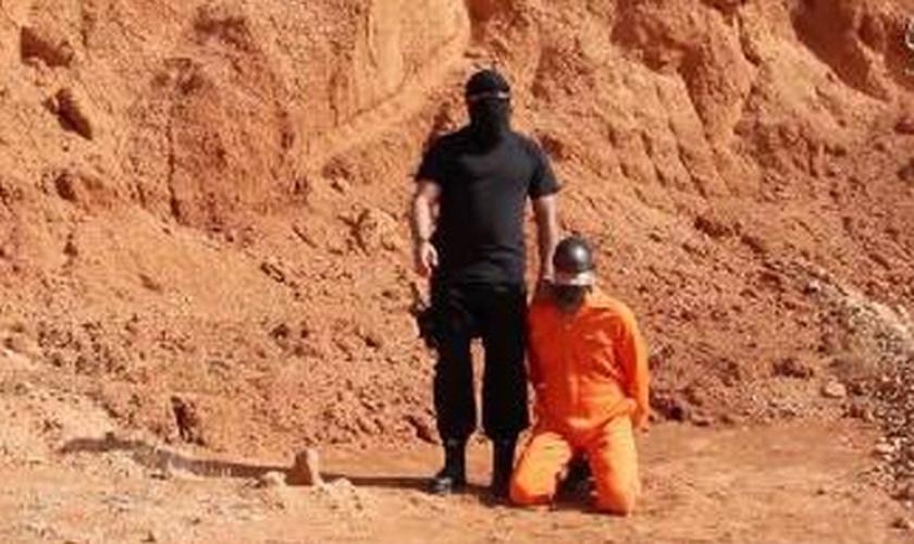 Na imagem, o terrorista envia uma mensagem ameaçadora aos cristãos e depois força a vítima a se ajoelhar para ser degolada. (captura de tela)