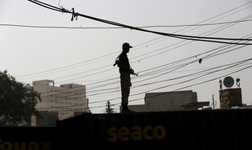 Soldado faz a segurança no terraço de prédio no Paquistão (Foto: Reuters)