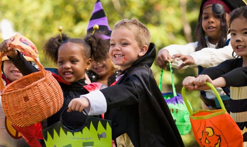 Crianças estendem suas sacolas para ganhar doces, durante festas do Halloween.