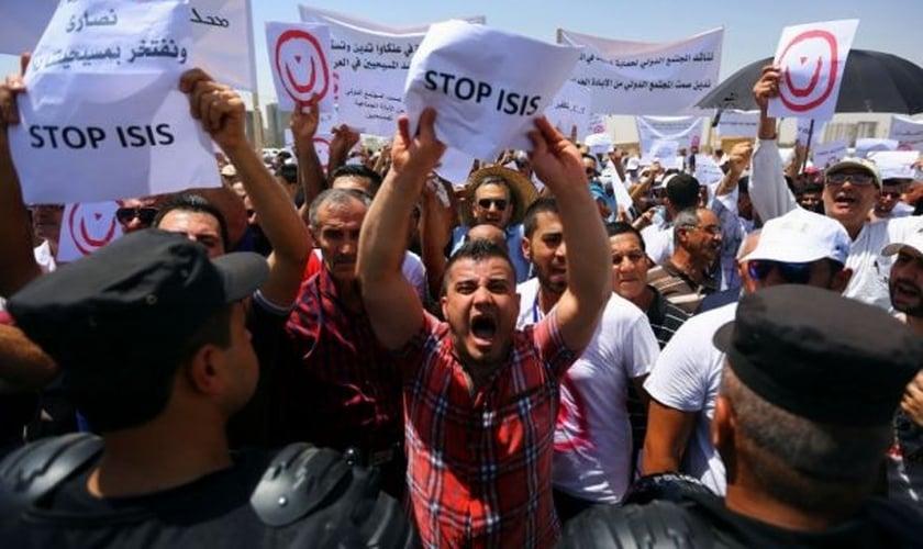 Cidadãos iraquianos seguram cartazes e placas durante protesto contra ações do Estado Islâmico, em 2014. (Foto: Reuters/Stringer)