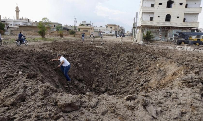 Homem sai de uma cratera causada pelo que, segundo ativistas, foi aberta pelo lançamento de bombas das forças leais ao presidente da Síria, Bashar Al-Assad. (Foto: Reuters)