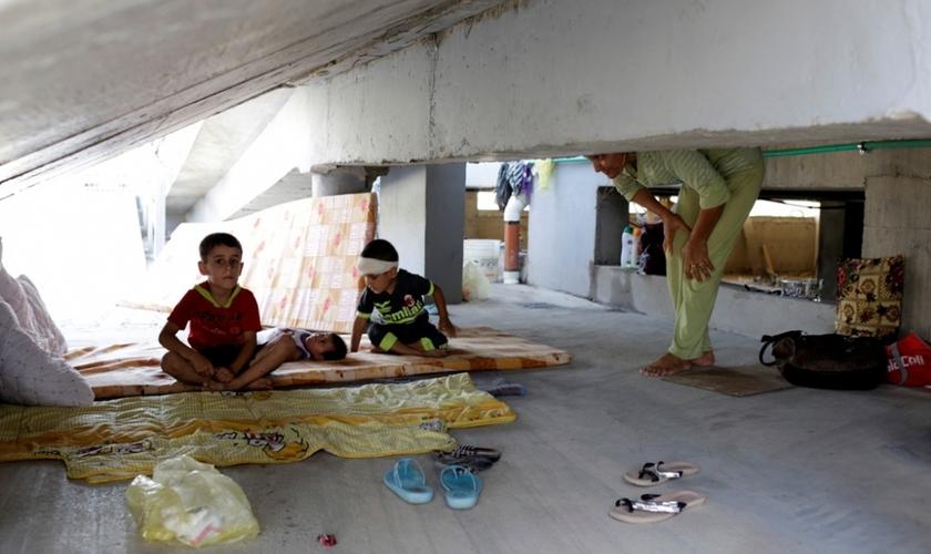 Crianças cristãs que fugiram da violência do Estado Islâmico em Qaraqosh, descansam sobre colchões velhos, em prédio abandonado, na região de Arbil - norte de Bagdá. (Foto: Reuters)