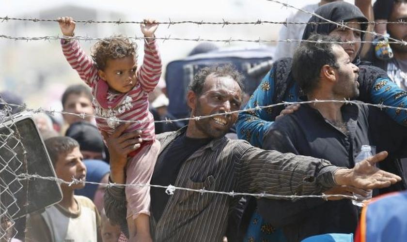 Refugiado sírio segura sua filha, enquanto tenta cruzar a fronteira da Turquia (Foto: Reuters)
