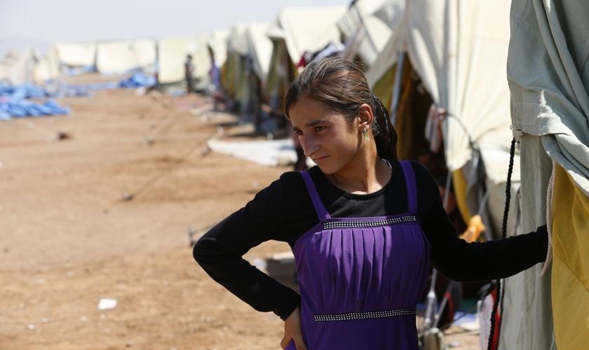 Após conseguir fugir de cativeiro do Estado Islâmico, garota yazidi permanece em frente à sua tenda, em um campo de refugiados na fronteira entre Curdistão e Síria (Foto: Youssef Boudlal / Reuters)