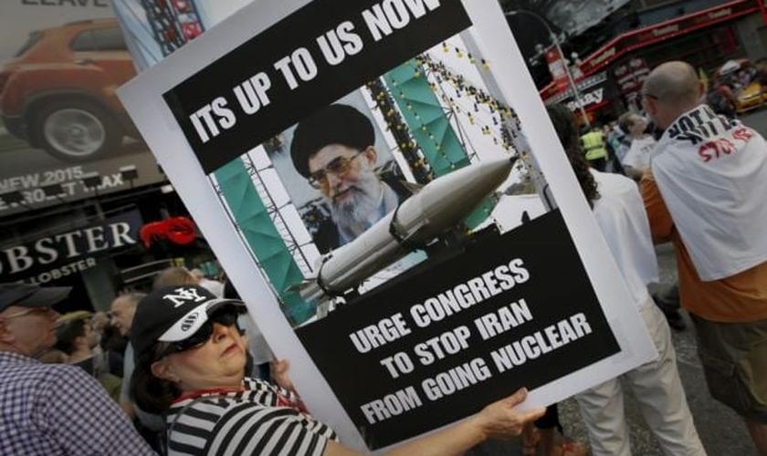Mulher segura placa em protesto contra o acordo nuclear entre as potências mundias e o Irã. (Foto: Mike Segar / Reuters)