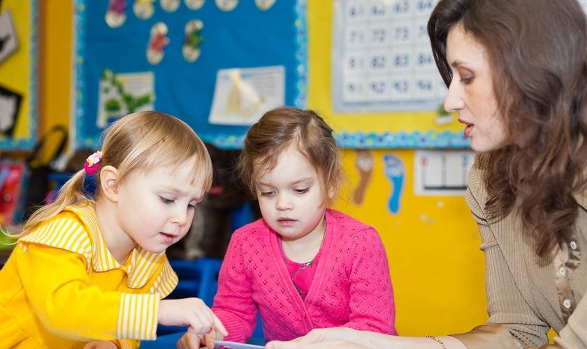 Professora ajuda crianças em sala de aula (Imagem: Istok)
