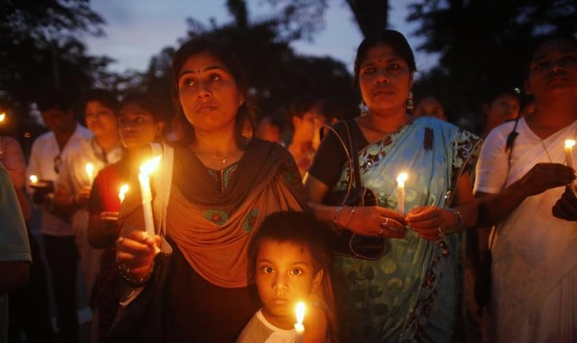 Membros da associação cristã de Bangladesh participam de cerimônia de homenagem às vítimas de uma explosão de bomba. (Foto: Reuters/ Andrew Biraj).