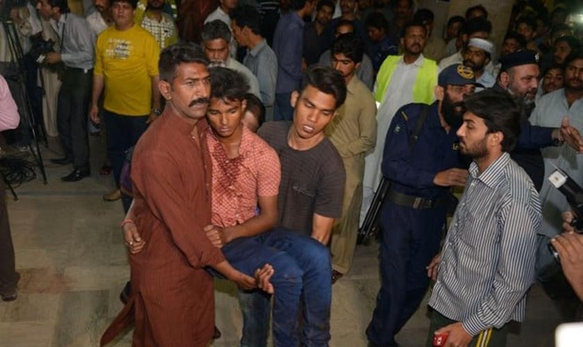 Vítima da explosão sendo socorrida depois que uma bomba explodiu em um parque público no Paquistão. (Foto: Arif Ali/AFP)