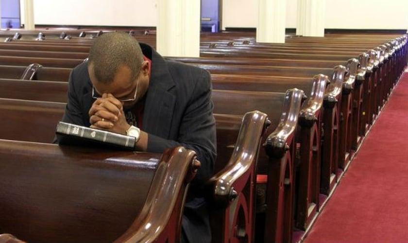 Pastor ora sozinho em igreja. (Foto: Olisa)