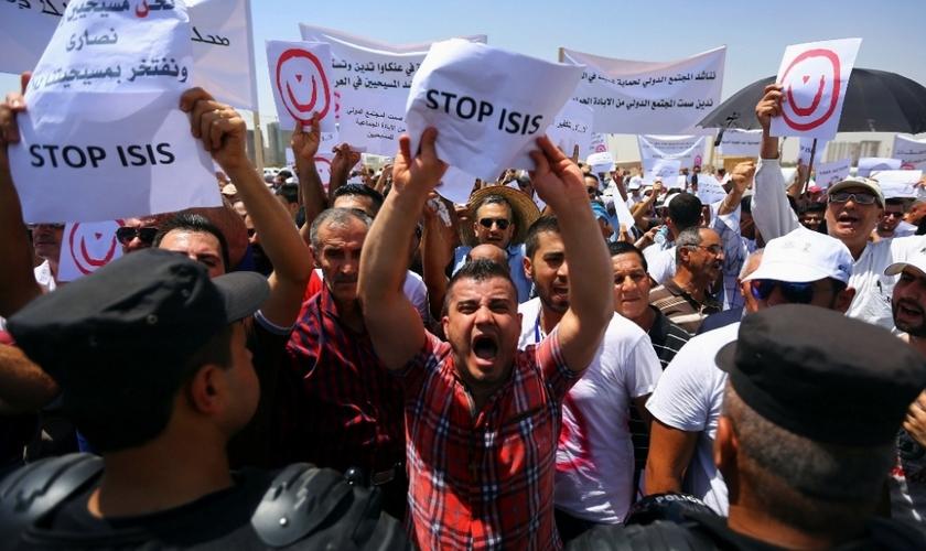 Manifestantes seguram placas e cartazes em protesto contra o Estado Islâmico no Iraque. (Foto: Reuters)
