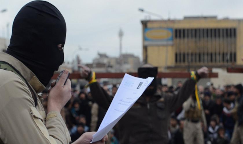 Terrorista do Estado Islâmico lê sentença de 'espiões' durante a crucificação dos mesmos. (Imagem: Captura de Tela)