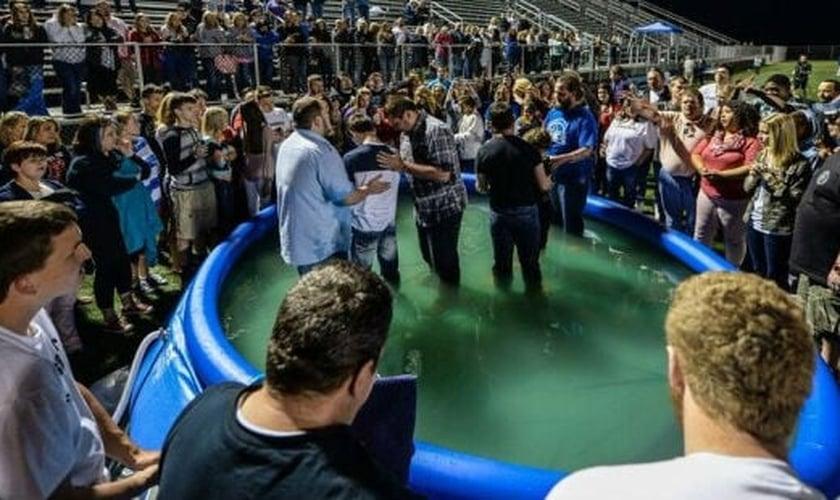 Estudantes sendo batizados em pscina inflável na escola. (Foto: Wes Wilson Photography).
