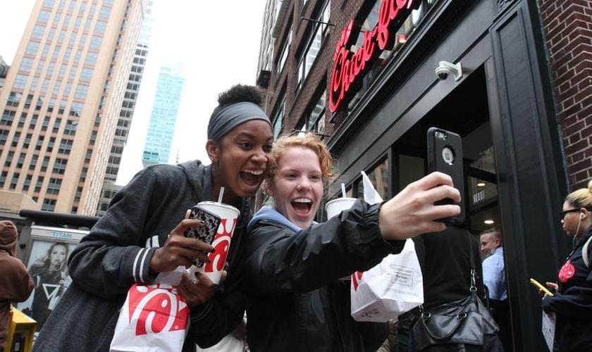 A jovem Jaimie Cranford (à direita) tira uma selfie com Mariah Reives (esquerda), exibindo sorrisos e seus lanches da rede lanchonetes fundadas por cristãos. (Foto: Tina Fineberg / AP Photo)