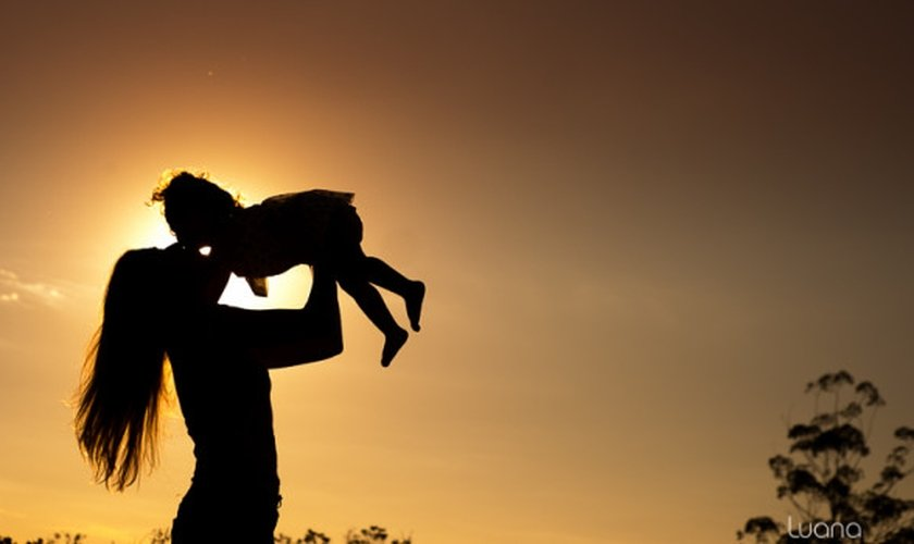 Mãe levanta a filha nos braços durante um por do sol. (Foto: Luana Okaeda)