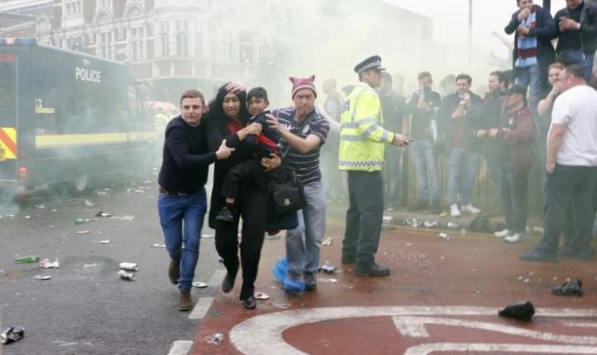 Imagem registrou momento em que Paul Sanderson (à direita) e outro homem ajudaram mãe e filho a fugir do tumulto gerado por torcedores antes de um jogo de futebol na Inglaterra. (Foto: Reuters)