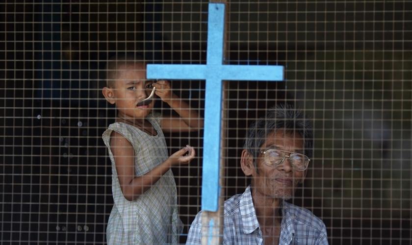 Homem e criança de família cristã olham pela janela de sua casa nos subúrbios de Yangon, em Myanmar. (Foto: Reuters/Damir Sagolj)