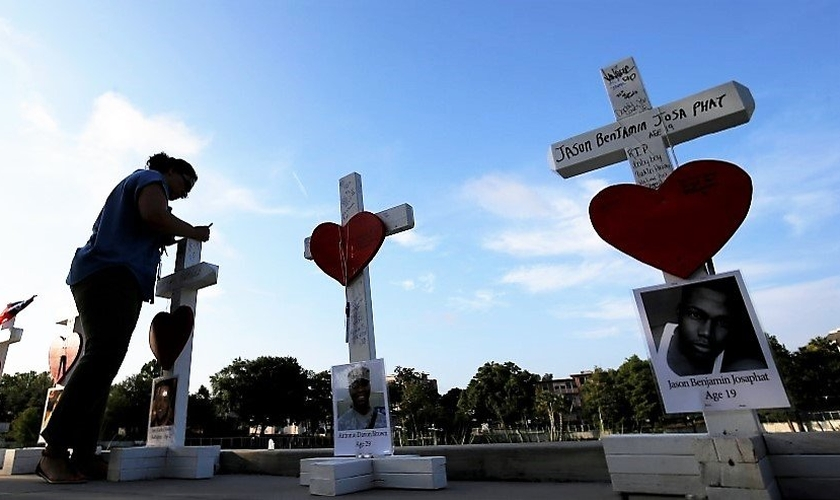 Mulher escreve uma mensagem em uma cruz em honra daqueles que foram mortos na boate gay 'Pulse', em Orlando. (Foto: Reuters)