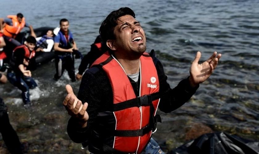 Homem ora após pisar em terra firme na ilha grega de Lesbos, depois de atravessar o mar. (Foto: Aris Messinis/AFP)