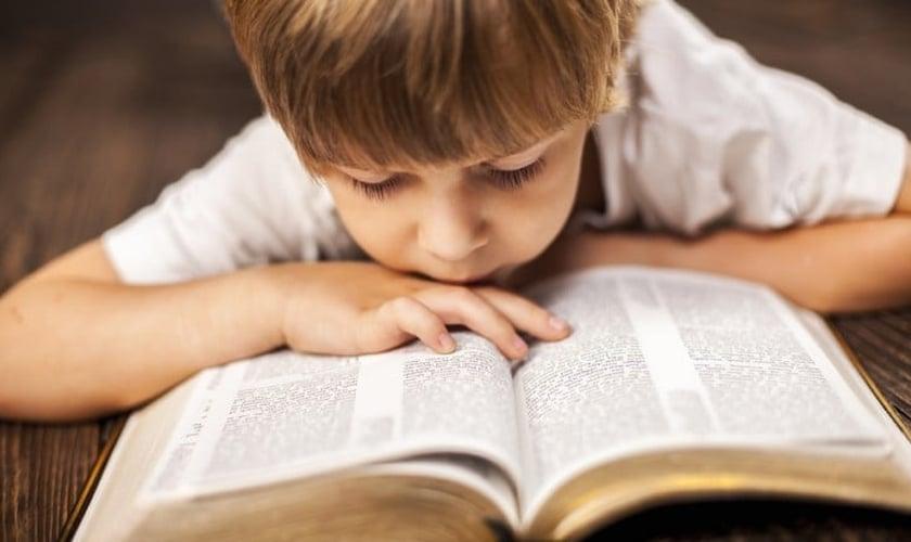 Garoto se debruça sobre Bíblia aberta. (Foto: Aim Lower Journal)