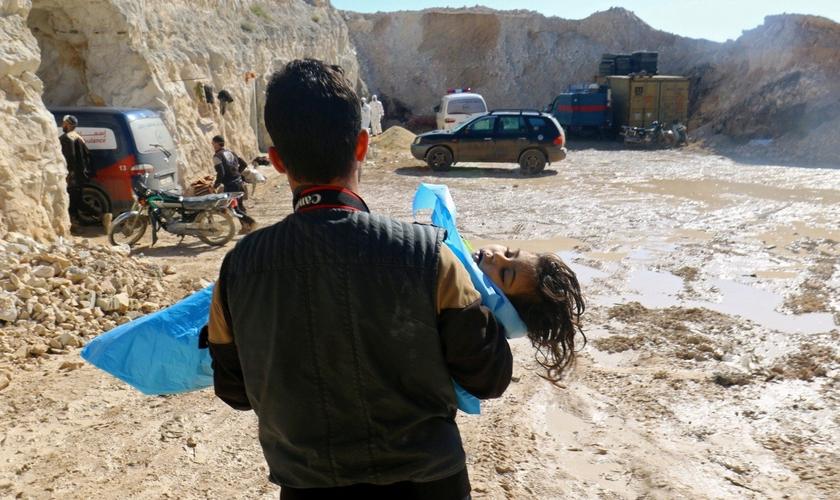 Homem carrega o corpo de uma criança morta após ataque químico em Khan Sheikhoun. (Foto: Ammar Abdullah/Reuters)