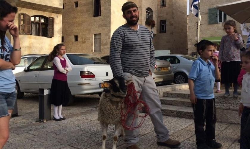 Homem segura cordeiro separado para simulação de sacrifício de Páscoa. (Foto: Times Of Israel)